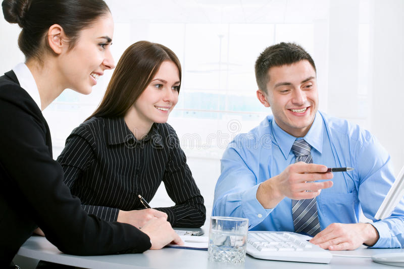 Workteam. Successful businessman and his pretty colleagues looking at monitor of computer stock image