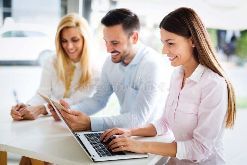 Workteam dans le bureau travaillant ensemble sur l'ordinateur portable images stock
