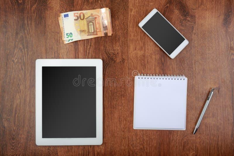 Worktop hoogste mening witte tablet en smartphone met het leeg scherm, een geld, een blocnote met pen en een geld royalty-vrije stock afbeelding