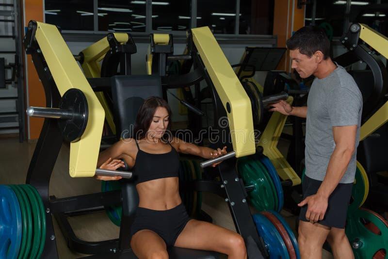 Workuot de femme sur la machine d'exercice avec l'instructeur photos stock