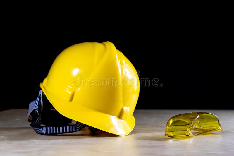 Workwear, helmet, gloves and glasses on a wooden working table. stock photography