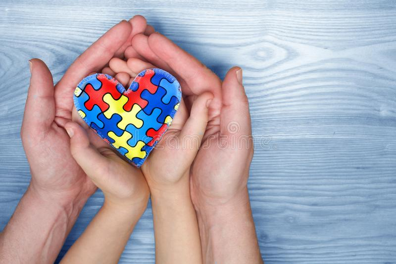 World Autism Awareness day, puzzle or jigsaw pattern on heart with autistic child`s and father hands stock images