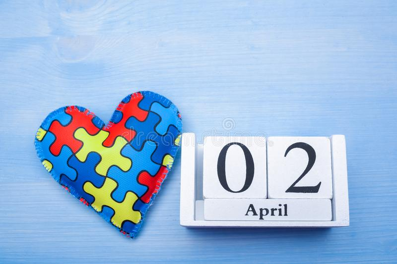World Autism Awareness day, mental health care concept with puzzle or jigsaw pattern on heart with calendar royalty free stock images