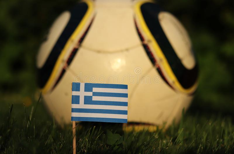 World Championship 2022. Euro 2020. Greek national flag. Greek soccer team. State flag of Greece on wooden stick in soccer field.  royalty free stock photos