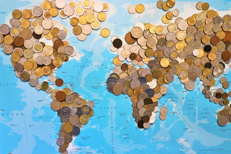 World coins assortment. World coins assortment with a map of the world in the background. Concept of world economy royalty free stock photo