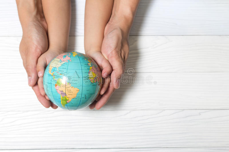 World concept: Two human hands holding global on wooden background. stock image