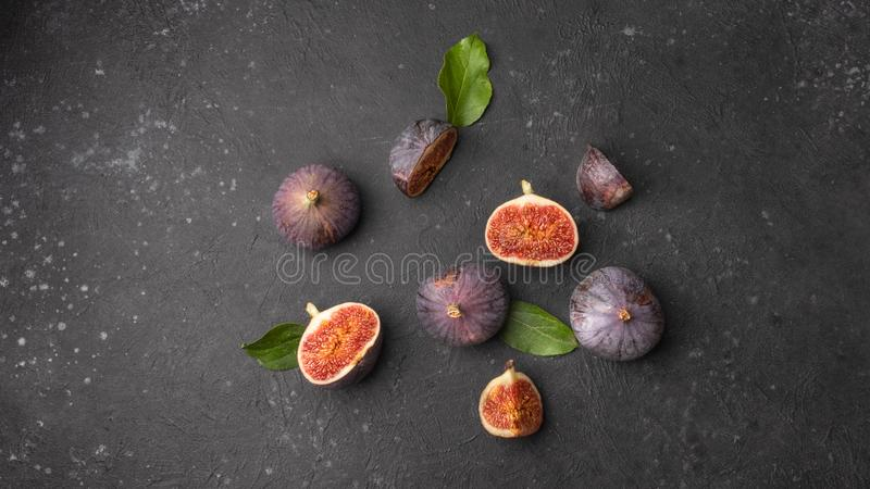 World food day. Ripe sweet figs with green leaves on a black background. The concept of a raw food diet and healthy lifestyle. Top stock photos