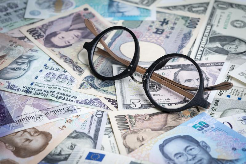 World, global or international financial analysis concept, eyeglasses on pile of major countries banknotes, can be use as forex m. Oney exchange trading stock photos