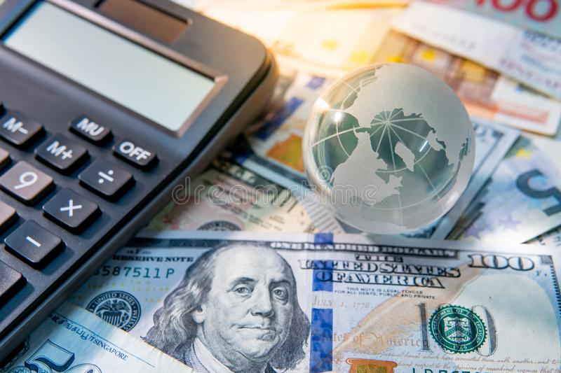 World globe crystal and calculator on banknotes royalty free stock images
