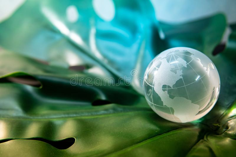 World globe crystal glass on green leaf. World globe cystal glass on green lush leaf. Environmental conservation. World environment day. Global business for royalty free stock images