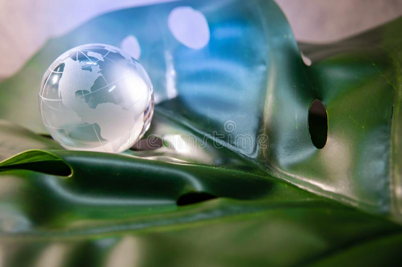 World globe crystal glass on green leaf. World globe cystal glass on green lush leaf. Environmental conservation. World environment day. Global business for stock photo