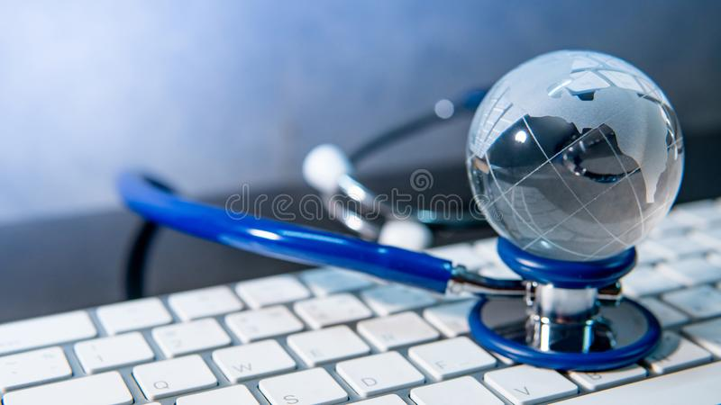 World globe on stethoscope and keyboard royalty free stock photo
