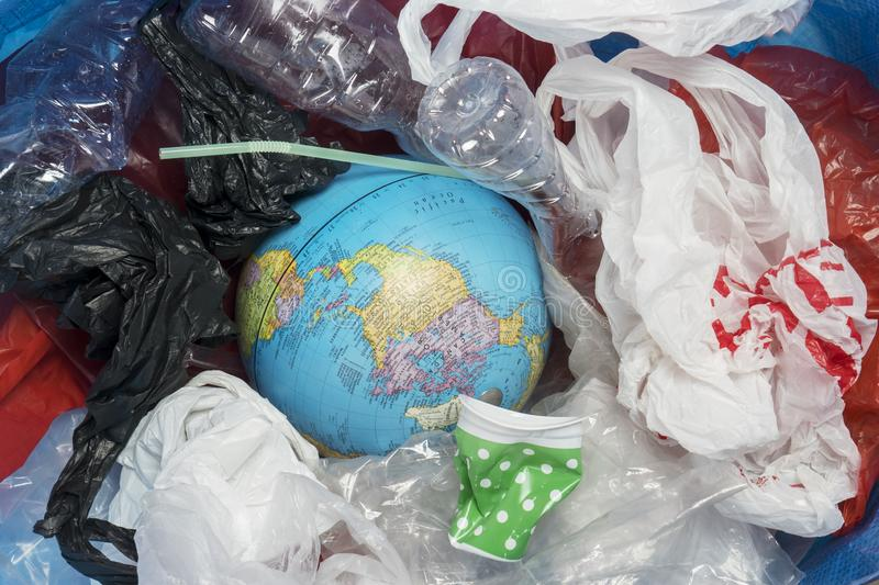 World globe with waste plastic in trash bin. Concept of save earth from plastic waste pollution. World globe with waste plastic in the trash bin stock image
