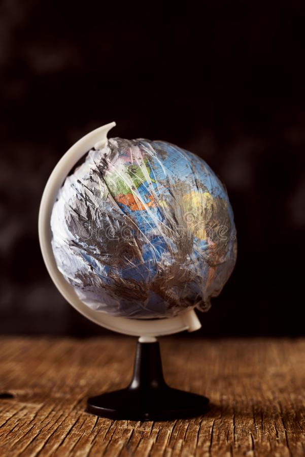 World globe wrapped in a dirty plastic royalty free stock photography