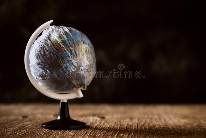 World globe wrapped in a dirty plastic stock photo