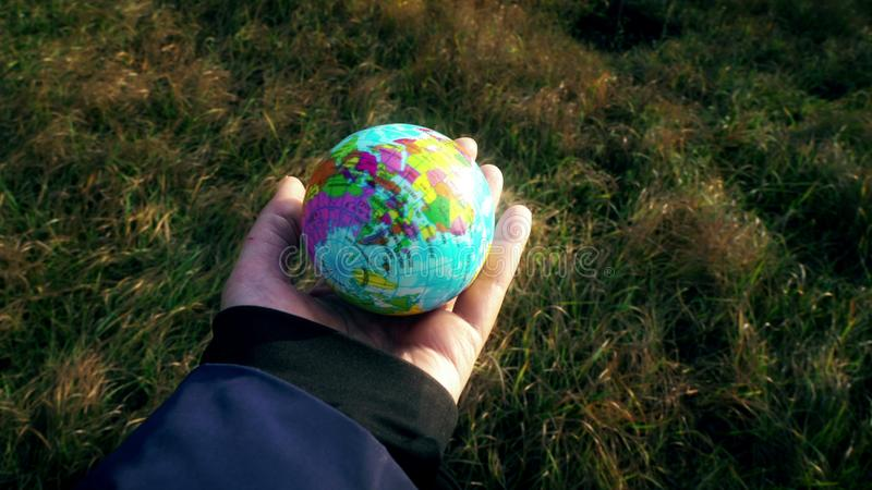 World in hand, female hand holding planet globe earth outside on grass background, human influence, ecological, climate royalty free stock image