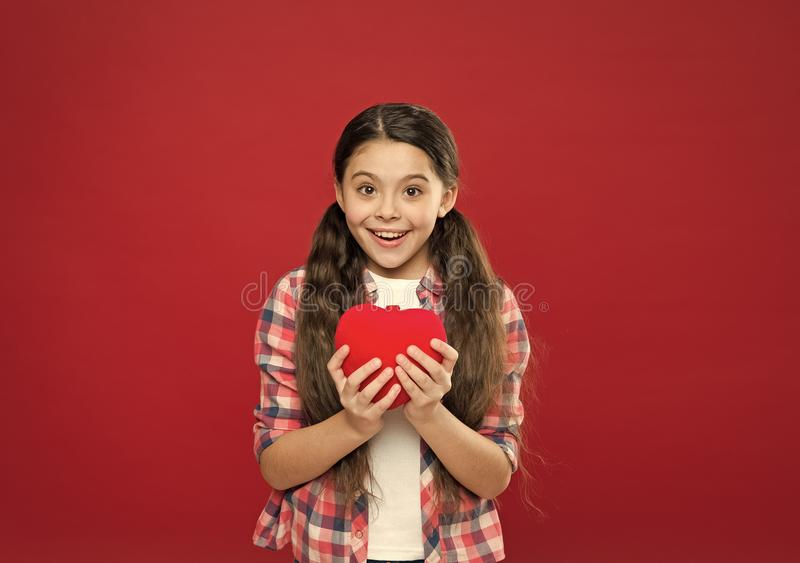 World health day. Little girl holding big red heart. Little child expressing love on valentines day. Cute girl in love. Having heart problem and heartache stock photo