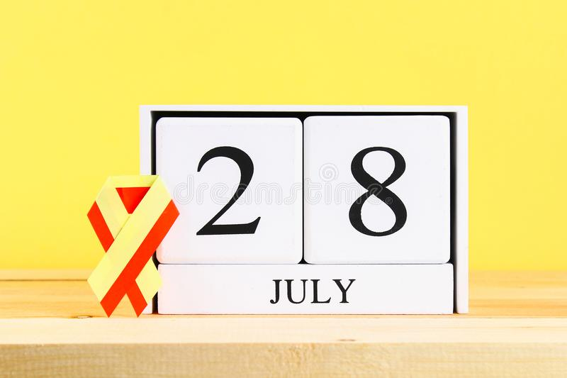 World Hepatitis Day. A wooden white calendar showing June 28 on a wooden table against a yellow wall background. Red yellow ribbon stock image