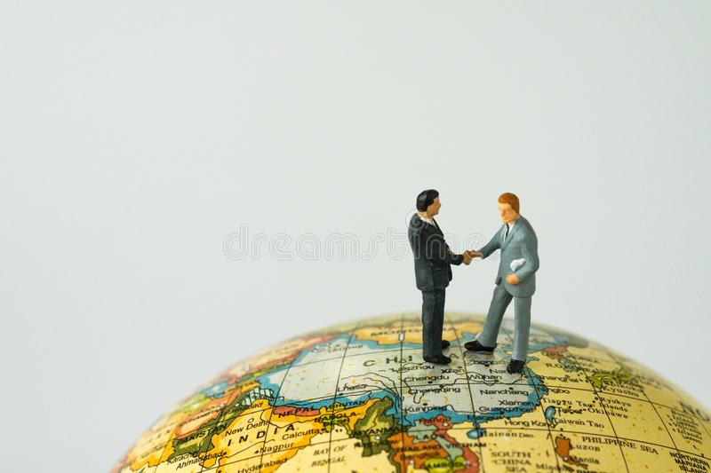 World leaders agreement hand shake teamwork concept with miniature business leaders hand shaking standing on globe map with copy. Space white background royalty free stock photo