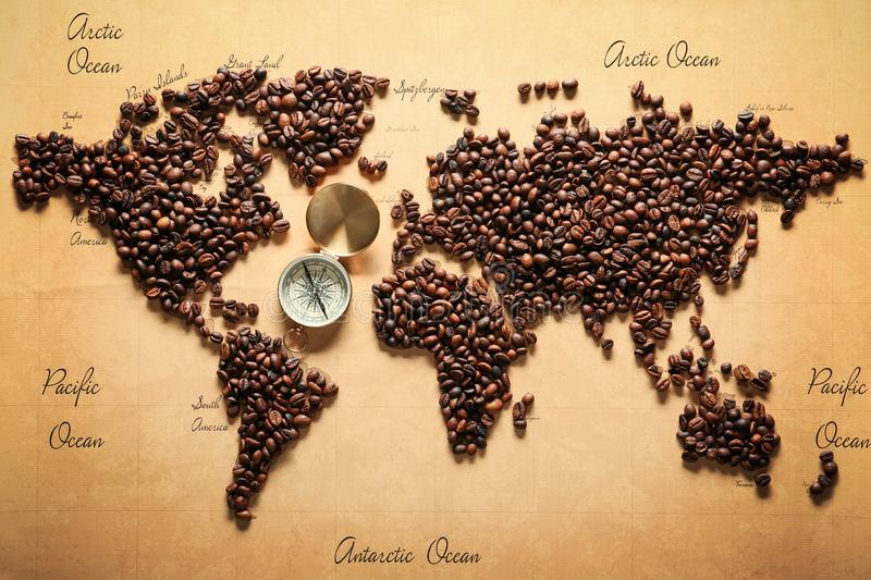 World map made of roasted coffee beans with compass, top view stock photo