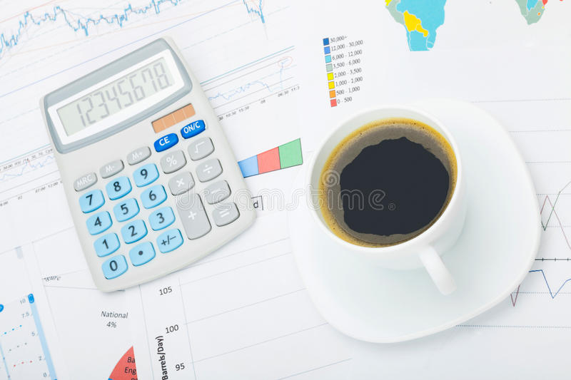 World map and some financial charts under coffee cup and calculator stock photo