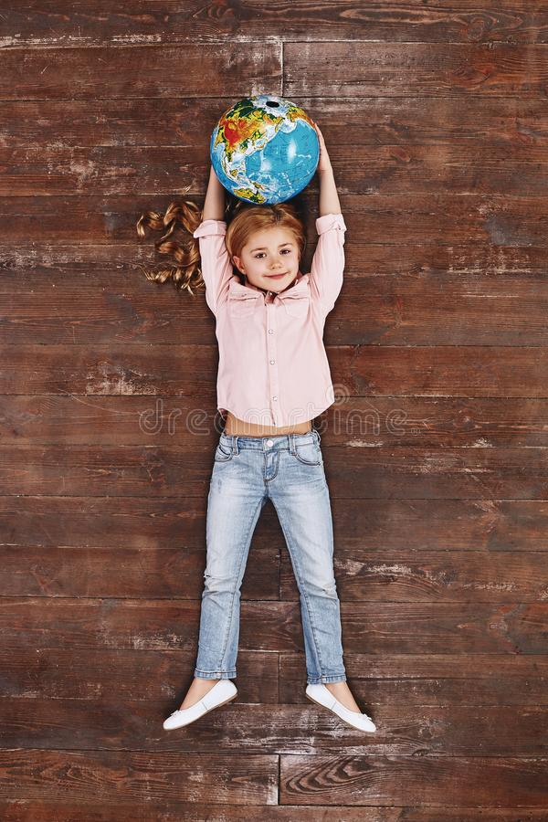 The world is mine. Girl holding globe, looking at camera and smiling royalty free stock image