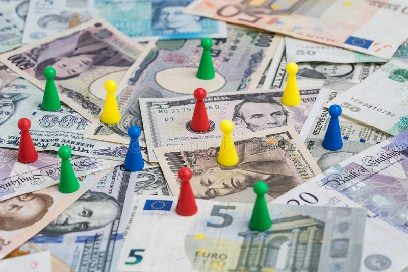 World money game by colorful plastic game figurines on international major countries banknotes, US dollar, Japanese yen, Euro, Ch stock image