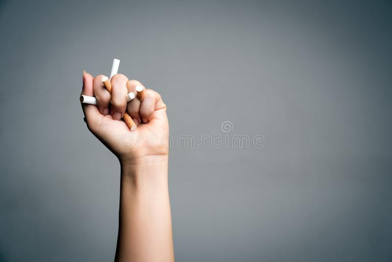 World No Tobacco Day, May 31. STOP Smoking. Close up Man hand crushing and destroying cigarettes on gray background royalty free stock photos