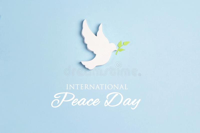 World Peace Day greeting card. Dove of peace with olive branch on a blue background royalty free stock photo