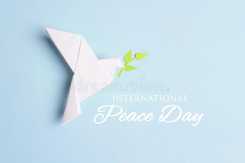 World Peace Day greeting card. Paper origami dove of peace with olive branch on a blue background stock photography