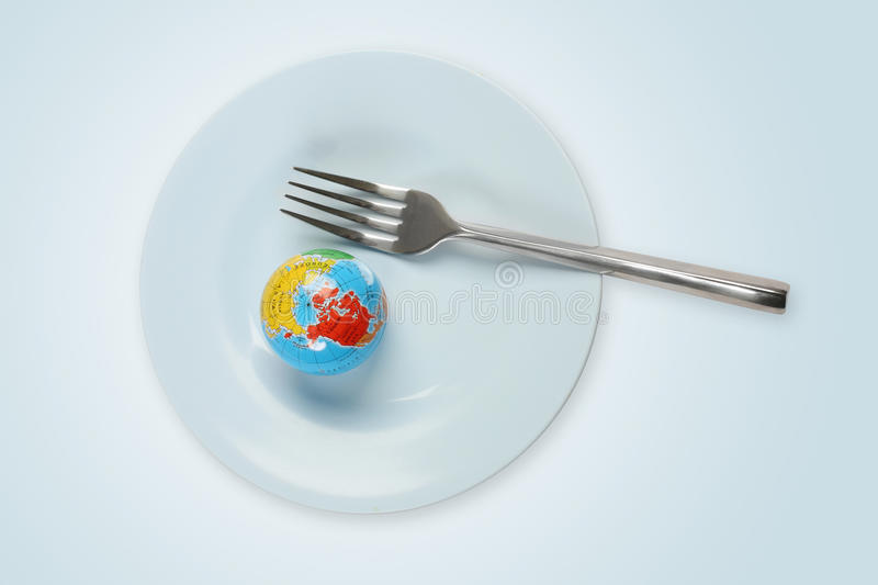 World in a plate with fork. In light blue background royalty free stock photo