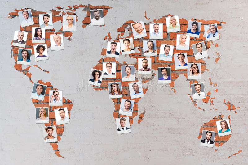 World population. Close-up image of brick world map with photographs of different people royalty free stock photo