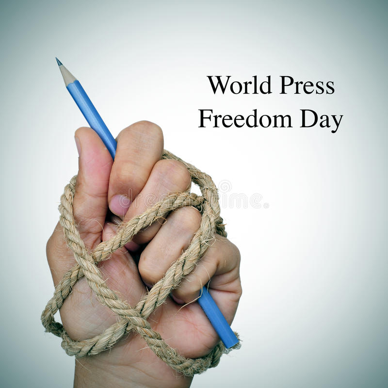 World press freedom day. The text world press freedom day and the hand of a man, completely tied with rope, holding a pencil, depicting the idea of oppression or stock photography