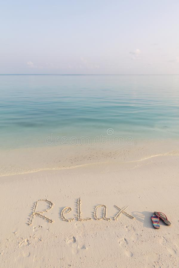 .World RELAX written on sand early in the morning on cristal clean beach of Maldives stock images