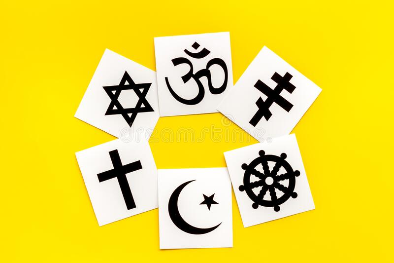 World religions concept. Christianity, Catholicism, Buddhism, Judaism, Islam symbols on yellow background top view.  royalty free stock photo