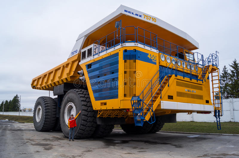World's Largest Huge Truck BelAZ with man for scale. Žodzina, Belarus - March 9, 2016: Haul truck BelAZ 75710 by Belarusian manufacturer BelAZ at trade show royalty free stock photography