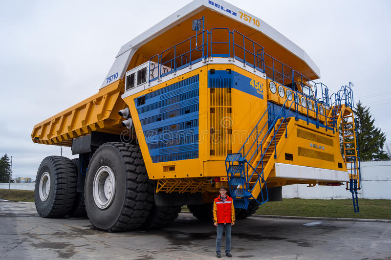 World's Largest Huge Truck BelAZ with man for scale. Žodzina, Belarus - March 9, 2016: Haul truck BelAZ 75710 by Belarusian manufacturer BelAZ at trade show stock image