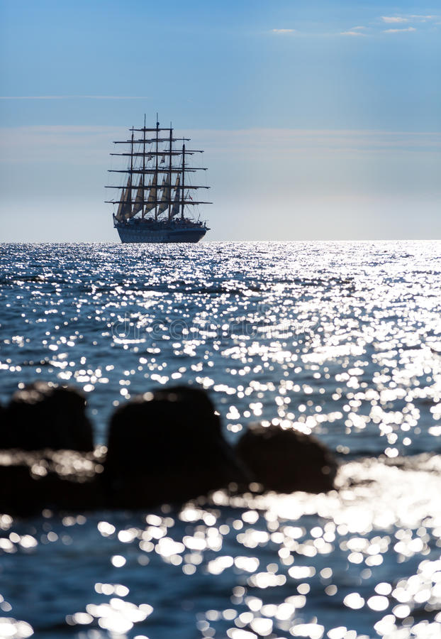 The world`s largest sailing ship leaves at sunset in the open sea. The world`s largest sailing ship with five masts leaves at sunset in the open sea royalty free stock images