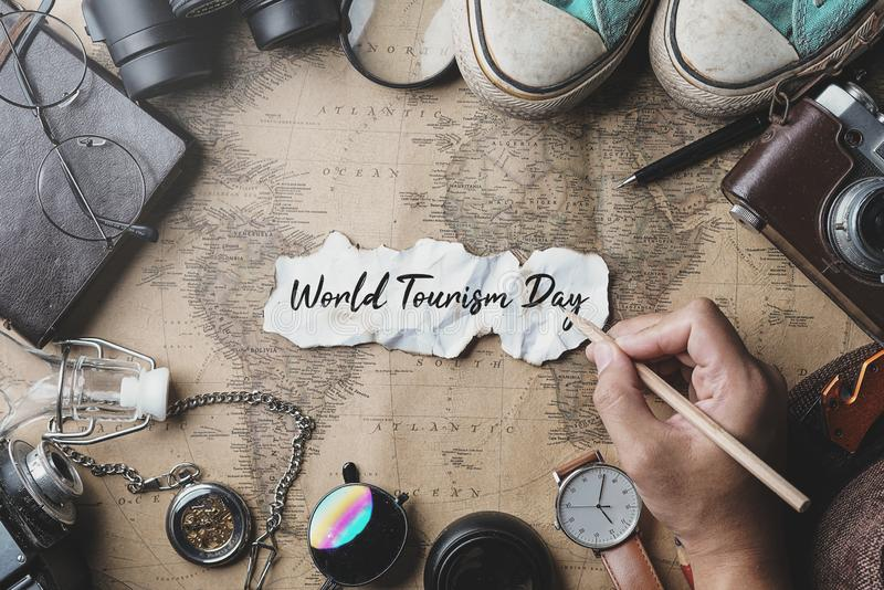World Tourism Day Hand Writing. Travel Concept Background. Overhead View of Traveler`s Accessories on Old Vintage Map royalty free stock image
