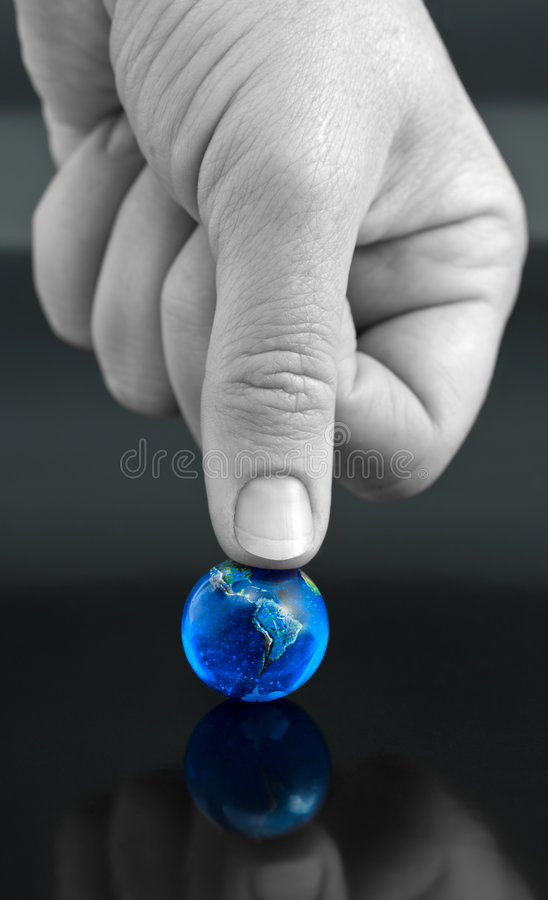 The World - Under my Thumb. Thumb Pressing Down on Bright Blue Marble Globe stock photos