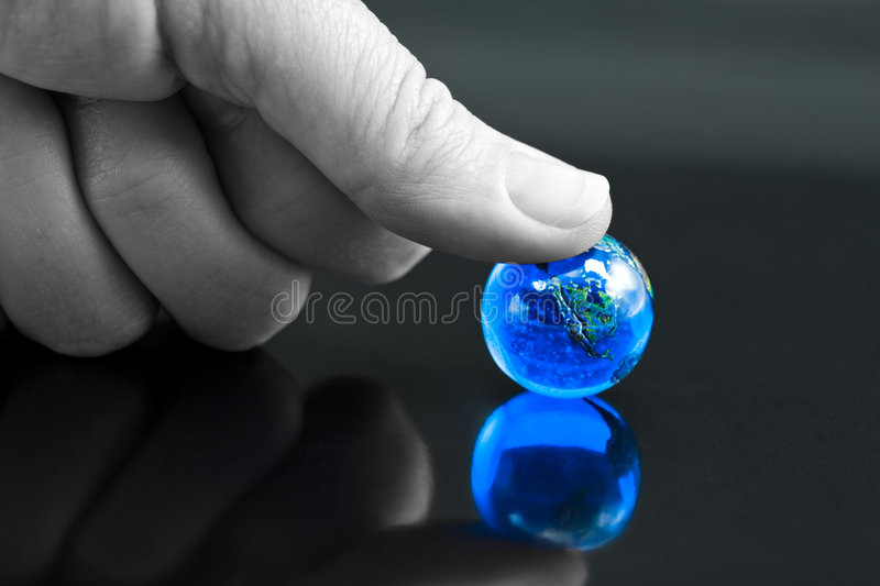 The World - Under my Thumb. Thumb Pressing Down on Bright Blue Marble Globe stock photo