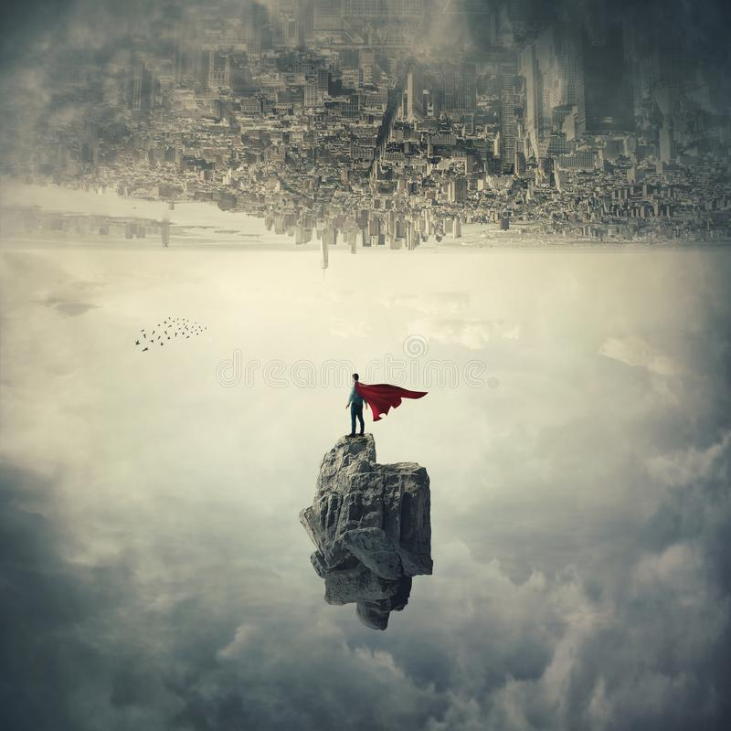 World upside down. Confident superhero with red cape standing on a levitating stone underneath the cityscape. Imaginary world upside down, mystical scene flying royalty free stock photos