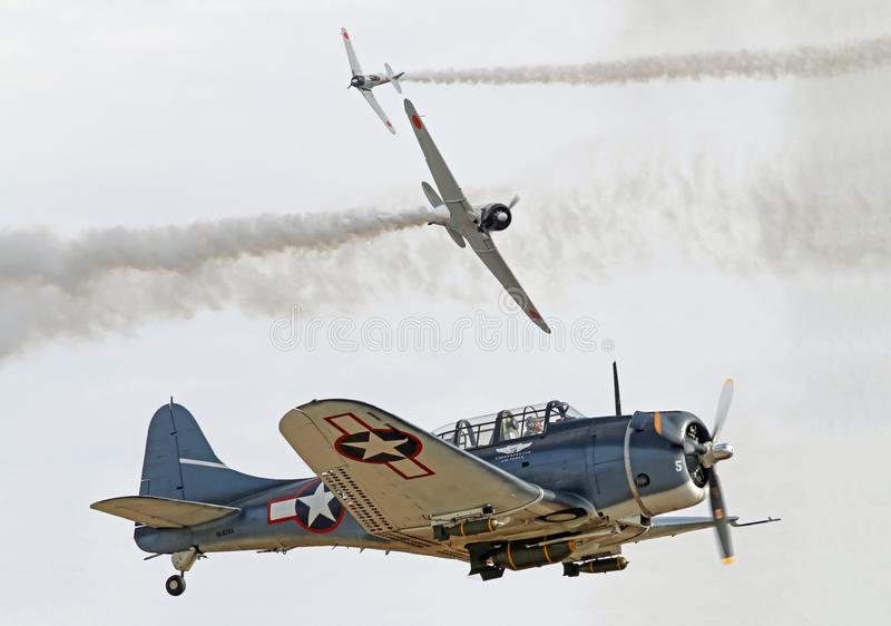 World War II Aerial Dogfight. Two Japanese Zero fighters pursue a U.S. Douglas SBD Dauntless dive bomber in a recreation of the Battle of Midway during World War royalty free stock photo