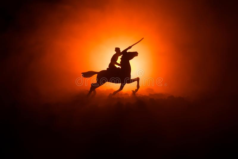 World war officer (or warrior) rider on horse with a sword ready to fight and soldiers on a dark foggy toned background. Battle sc. Ene battlefield of fighting royalty free stock photography