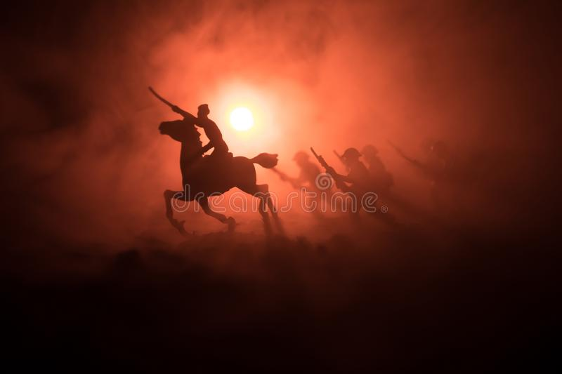 World war officer (or warrior) rider on horse with a sword ready to fight and soldiers on a dark foggy toned background. Battle sc. Ene battlefield of fighting stock image