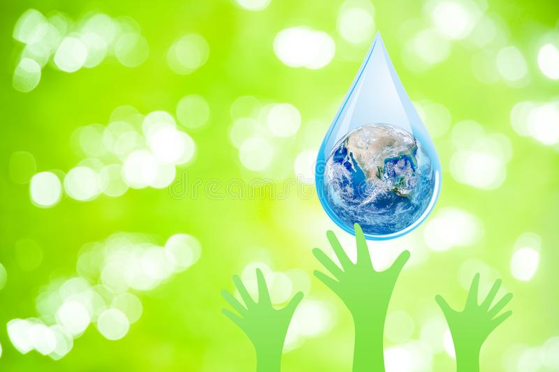 Blue planet earth globe in water drop falling to many green hands. World Water Day Concept : Blue planet earth globe in water drop falling to many green hands stock image