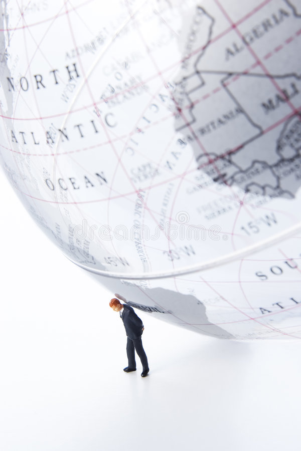 World on your shoulders. Business figurine placed next to globe royalty free stock photography