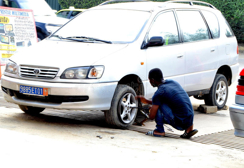 WORLDWIDE DAY TO COMBAT COUNTERFEITING. Young African during the world day of counterfeiting getting rid of counterfeit tires from his car launching a strong stock photography