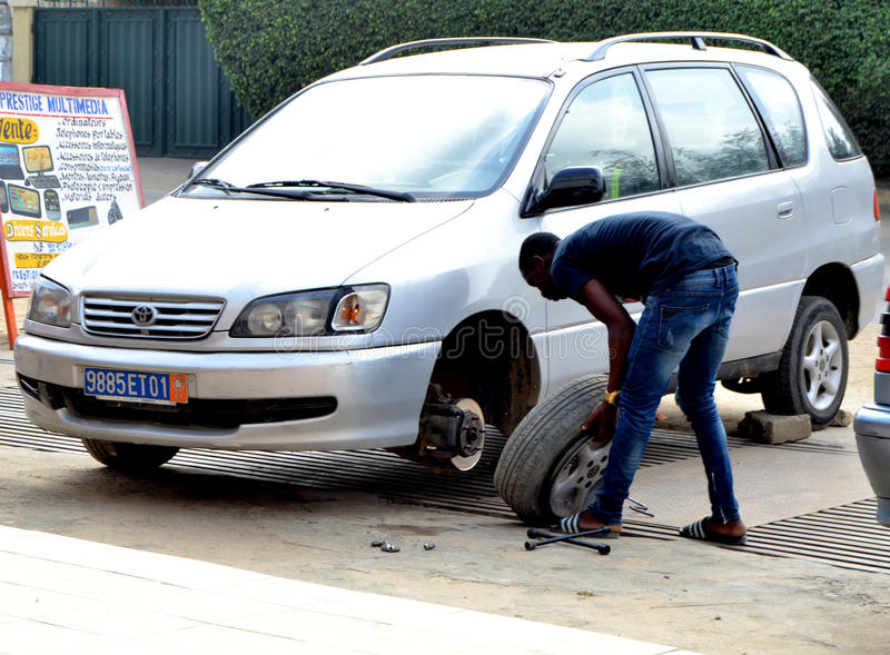 WORLDWIDE DAY TO COMBAT COUNTERFEITING. Young African during the world day of counterfeiting getting rid of counterfeit tires from his car launching a strong stock photo