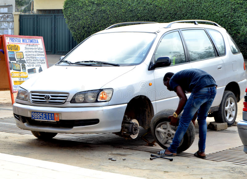 WORLDWIDE DAY TO COMBAT COUNTERFEITING. Young African during the world day of counterfeiting getting rid of counterfeit tires from his car launching a strong stock image